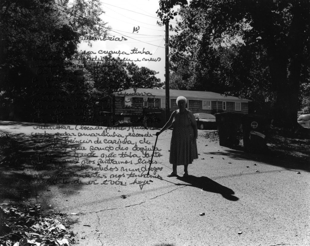 An older woman walking along a driveway with a cane. There is black text overlaid on the image.
