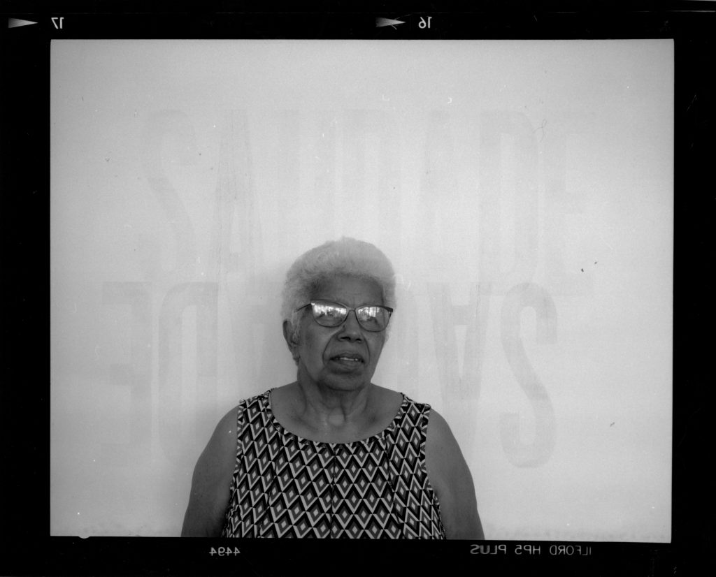 "A woman barely smiles, looking into the distance. The word ""Saudade"" is on the wall behind her both upright and upside down."